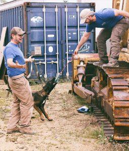 RMSDA handler Roy Scholl and RMSDA Director Stephen Burton reward puppy Pelham for a successful beginner runaway exercise